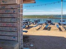 Openlucht witte houten die paneelmuur in kleurrijke graffiti wordt behandeld stock afbeelding