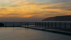 Openlucht zwembad door de oceaan bij dageraad Stock Afbeelding