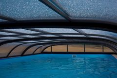 Openlucht zwembad met dakbouw en natte dalingen op het Stock Afbeeldingen