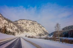 Openluchtdiemening van de winterweg met zwaar sneeuw en ijs in de bos en kleine rivier aan één kant van de weg wordt behandeld Royalty-vrije Stock Foto