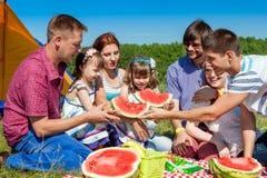 Openluchtgroepsportret van gelukkig bedrijf die picknick op groen gras in park hebben en van watermeloen genieten Stock Foto's
