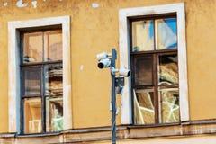 Openluchtkabeltelevisie-cameraveiligheidssysteem bij de gele muurbouw royalty-vrije stock afbeeldingen