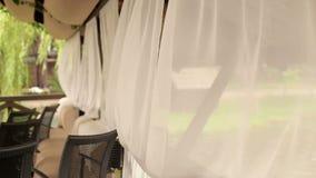 Openluchtkoffie met witte stromende gordijnen stock video