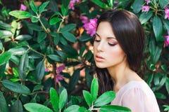 Openluchtmanierfoto van mooie jonge die vrouw door bloemen wordt omringd De Bloesem van de lente Stock Foto's
