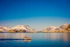 Openluchtmening van mensen die in een boot in een schitterende zonnige dag met blauwe hemel en reusachtige die berg varen met bin Royalty-vrije Stock Afbeeldingen