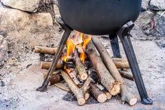 Openluchtopen haard onder een gietijzerpot met braadstukken Barbecuepartij stock afbeelding