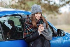 Openluchtportret die van jonge Kaukasische vrouw, een kop van meeneemkoffie in bospark op koude seizoendag houden Gekleed in een  Stock Fotografie
