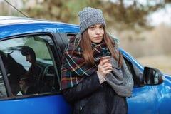 Openluchtportret die van jonge Kaukasische vrouw, een kop van meeneemkoffie in bospark op koude seizoendag houden Gekleed in een  Royalty-vrije Stock Foto
