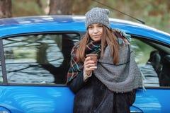 Openluchtportret die van jonge Kaukasische vrouw, een kop van meeneemkoffie in bospark op koude seizoendag houden Gekleed in een  Stock Foto's
