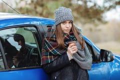 Openluchtportret die van jonge Kaukasische vrouw, een kop van meeneemkoffie in bospark op koude seizoendag houden Gekleed in een  Royalty-vrije Stock Afbeeldingen