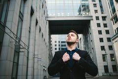 Openluchtportret van de jonge knappe mens met een baard tegen de achtergrond van moderne architectuur Royalty-vrije Stock Afbeeldingen