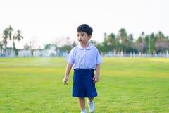 Openluchtportret van een Eenzaam Aziatisch studentenjong geitje in school eenvormige status stock foto