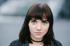 Openluchtportret van een jong modieus meisjesbrunette met blauwe mooie ogen en grote gevoelvolle ogen royalty-vrije stock afbeeldingen