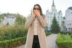 Openluchtportret van een jonge vrouw die haar mond behandelen met handen royalty-vrije stock foto's