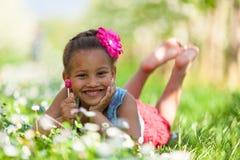 Openluchtportret van een leuk jong zwart meisje dat - Afrikaanse pe glimlacht stock afbeeldingen