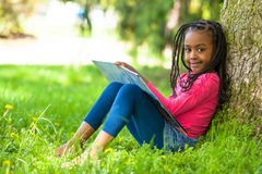 Openluchtportret van een leuk jong zwart meisje die een boe-geroep lezen royalty-vrije stock fotografie