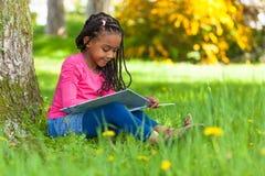 Openluchtportret van een leuk jong zwart meisje die een boe-geroep lezen Royalty-vrije Stock Foto's