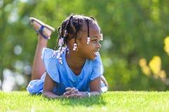 Openluchtportret van een leuk jong zwart meisje die op g liggen Stock Foto