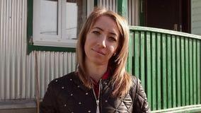 Openluchtportret van een tiener met oud verlaten huis op de achtergrond stock videobeelden