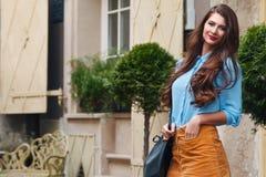 Openluchtportret van het jonge mooie gelukkige het glimlachen vrouw stellen op de straat Model dragende modieuze kleren Meisje stock afbeelding