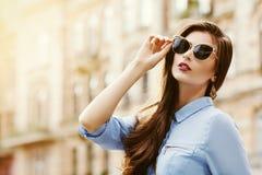 Openluchtportret van het jonge mooie zekere vrouw stellen op de straat Model dragende modieuze zonnebril Meisje royalty-vrije stock afbeelding
