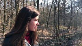 Openluchtportret van jong mooi Kaukasisch tienermeisje die en camera, bosweg op een winderige dag glimlachen onderzoeken stock video