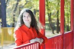 Openluchtportret van jonge vrouw die oranje laag dragen bij de achtergrond van het achtbaanpark royalty-vrije stock fotografie