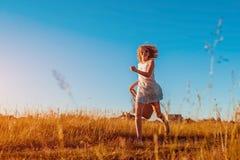 Openluchtportret van jonge vrouw met rood krullend haar die met een zak van bloemen lopen Gelukkige de zomervakantie stock foto's