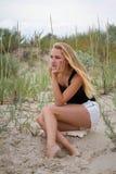 Openluchtportret van melancholische en droevige jonge mooie vrouwenzitting op het zand dichtbij het alleen overzees Stock Foto