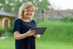 Openluchtportret van rijpe bedrijfsvrouw met digitale tablet, groene tuin als achtergrond van een privé woonplaats royalty-vrije stock foto's