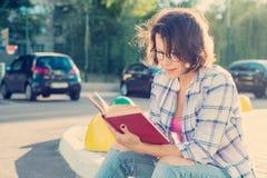 Openluchtportret van rijpe vrouw in glazen met een boek stock foto
