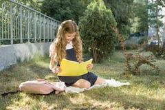 Openluchtportret van schoolmeisjezitting op het de schoolnotitieboekje van de graslezing Begin de school royalty-vrije stock afbeelding