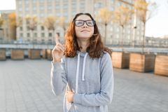 Openluchtportret van slim tienermeisje met glazen die wijsvinger op idee, eureka, gouden uur tonen royalty-vrije stock afbeeldingen