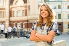 Openluchtportret van tiener 13, 14 jaar oud, meisje met gekruiste wapens, de achtergrond van de stadsstraat Stock Fotografie