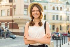 Openluchtportret van tiener 13, 14 jaar oud, meisje met gekruiste wapens, de achtergrond van de stadsstraat Royalty-vrije Stock Fotografie