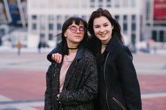 Openluchtportret van twee jonge, gelukkige, mooie en glimlachende meisjes in zonnebril Stock Foto's