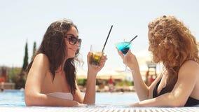 Openluchtportret van twee jonge leuke meisjes in zonnebril en zwempakken met cocktailglas het koelen in zwembad stock videobeelden
