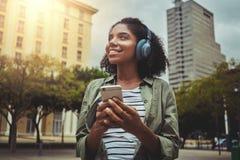 Openluchtportret van vrouw het luisteren aan muziek die mobiele telefoon met behulp van stock afbeelding