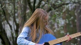 Openluchtprestaties in de groep van de aardmuziek De gelukkige kleine meisjes die en zingen liederen die het blauwe haar van de g stock video