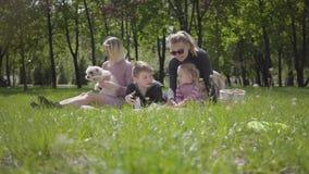 Openluchtrecreatie van de portret de aardige familie Twee mooie jonge moeders en hun kinderen bij een picknick in het park een jo stock footage