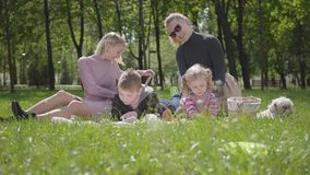 Openluchtrecreatie van de portret de jonge familie Twee mooie jonge moeders en hun kinderen bij een picknick in het park een jong stock video