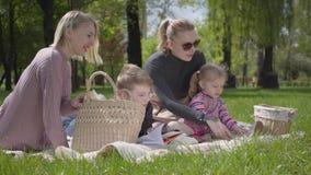 Openluchtrecreatie van de portret de leuke familie Twee mooie jonge moeders en hun kinderen bij een picknick in het park een jong stock footage