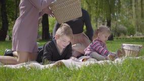 Openluchtrecreatie van de portret de mooie familie Twee mooie jonge moeders en hun kinderen bij een picknick in het park een jong stock videobeelden