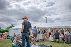 Openluchtscène van een levend muziekfestival die groepen families buiten een grote markttent in zomer tonen stock foto's