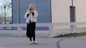 Openluchtschot van blonde het model stellen in een in grijze laag door het gebouw in de herfst stock footage