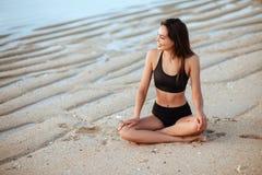 Openluchtschot van het glimlachen jong vrouwelijk model in bikini die zich tegen blauwe hemel bevinden stock foto's