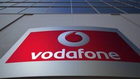 Openluchtsignage raad met Vodafone-embleem De moderne bureaubouw Het redactie 3D teruggeven Stock Afbeelding
