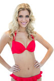Openly smiling blonde model posing with hands on hips in red bikini. On white background Royalty Free Stock Images