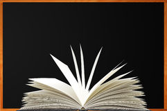 Openned book over blank blackboard with wood frame Royalty Free Stock Image
