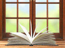 Openned book on wooden table and window and nature background Royalty Free Stock Images